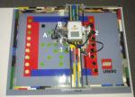 Foto eines Mühle spielenden Lego-Roboters auf einem speziell farbig markiertem, schematischen Mühlespielfeld