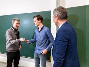 Bild von der Überreichung einer Urkunde von Prof. Freiling (links) und Prof. Teich (rechts) an Herrn Spieck (mitte)