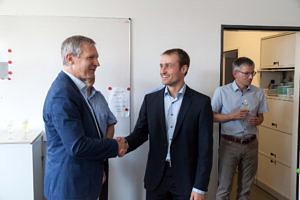 v. l.: Prof. Teich gibt S. Roloff die Hand, im Hintergrund sieht man Prof. Kaup