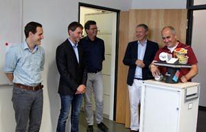 Der Doktorhut, auf einem Rollschrank positioniert, wird erklärt und bewundert; v.l.: Gutachter Prof. Hack (Univ. d. Saarlandes), Prof. Stamminger (FAU) und Prof. Teich, O. Reiche (2. v.l.) und Dr. Hannig (rechts)