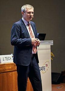 J. Teich auf dem Podium begürßt stehend im Rahmen des Openings die DATE 2019-Teilnehmer